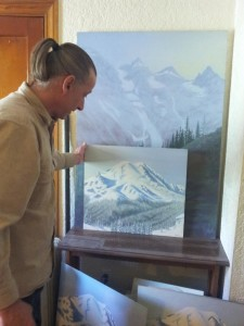 Kane shows off landcape paintings of Mt Rainier in his Garfield St Apartment. Photo by Carrie Reierson.